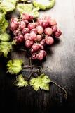 与叶子的葡萄在黑暗的土气木背景 库存图片