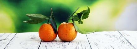 与叶子的蜜桔在木背景 普通话土气st 免版税图库摄影
