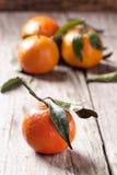 与叶子的蜜桔在木背景 免版税库存照片