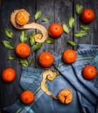 与叶子的整个和被剥皮的蜜桔在蓝色土气木背景 库存照片