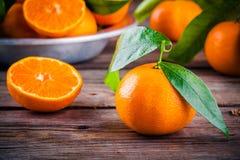 与叶子的水多的成熟蜜桔在木背景的一个碗 库存图片