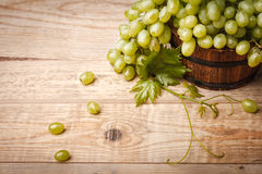 与叶子的绿色葡萄在木板 库存照片