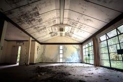 与叶子被撒布的地板的被放弃的修造的内部 免版税库存照片