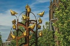 与叶茂盛树的金黄金属鸟纪念碑和尖顶在韦斯普的晴天 库存图片