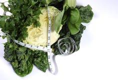 与叶茂盛绿色菜和卷尺的健康饮食健康食品 免版税库存照片