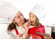 与吃巧克力块的小女儿的愉快的母亲烘烤用作为成份,当教孩子时 免版税库存照片