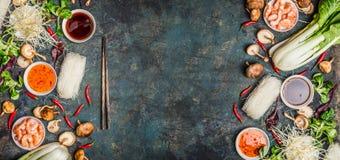 与各种各样的亚洲食物背景烹调在土气背景,顶视图的成份 库存图片
