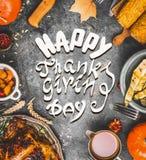与各种各样的传统盘的食物框架:火鸡、南瓜、玉米、调味汁和烤收获菜和文本愉快的感恩 库存图片