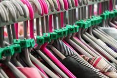 与各种各样的妇女衣物的衣架在旧货店,在M大小标记的细节 库存照片
