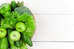 与各种各样的新鲜的未加工的绿色菜的白色木背景 图库摄影