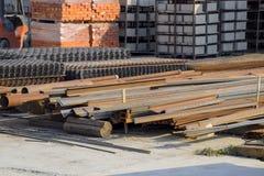 与各种各样的材料的大厦基地建筑的 金属化管子、角落和渠道,滤网 具体建筑和砖 免版税库存照片