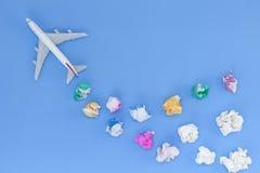 与各种各样的纸球的飞机模型在蓝色背景与 库存照片