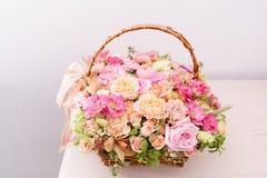 与各种各样的花的布置在柳条筐的颜色在桃红色桌上 美好的花束春天 明亮的室,白色 免版税图库摄影