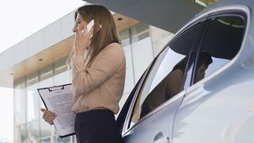 与合同的夫人经纪谈话与智能手机的,站立的近的汽车客户 股票视频