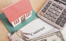 与合同纸的式样房子和美元金钱在桌上 贷款家财务概念 免版税库存照片