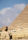 与吉萨棉埃及金字塔的古老狮身人面象在背景中 库存图片