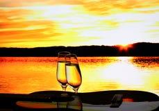 与吉他的两块香槟玻璃在日落 免版税库存图片