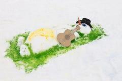 与吉他说谎的晒日光浴的雪人 库存照片