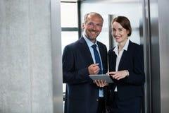 与同事的商人电梯的 免版税库存图片