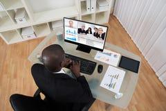 与同事的商人视讯会议在计算机上 免版税库存图片