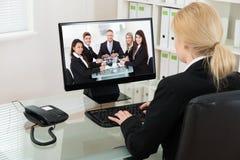 与同事的女实业家视讯会议在计算机上 免版税库存照片