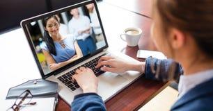 与同事的女实业家视讯会议膝上型计算机的 免版税库存照片