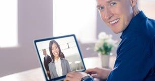 与同事的微笑的商人视讯会议膝上型计算机的在办公室 免版税库存图片