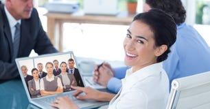 与同事的微笑的女实业家视讯会议在办公室 免版税库存图片