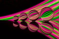 与后边五颜六色的霓虹照明设备的霓虹水晶球 图库摄影