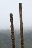 与后边有薄雾的森林的传统Gitxsan图腾柱 免版税库存图片