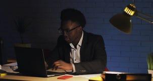 与后运作在夜办公室的手提电脑和纸的年轻商人 E 影视素材
