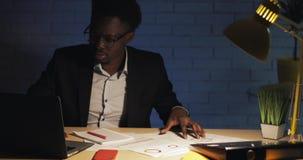 与后运作在夜办公室的手提电脑和纸的年轻商人 E 股票视频