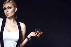 与向后拉的头发的一个白肤金发的模型和发烟性眼睛化妆与拿着一杯白兰地酒的悬挂装置的佩带的白色上面 免版税图库摄影