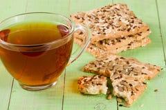 与向日葵、胡麻和芝麻籽种子的酥脆面包与一杯茶在绿色木背景 库存图片