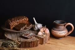 与向日葵种子、杯子牛奶,麦子大蒜和词根,坚果,健康吃的概念的黑暗的谷物面包,在一木backg 免版税图库摄影