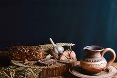 与向日葵种子、杯子牛奶,麦子大蒜和词根,坚果,健康吃的概念的黑暗的谷物面包,在一木backg 库存照片