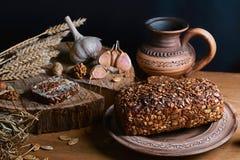 与向日葵种子、杯子牛奶,麦子大蒜和词根,坚果,健康吃的概念的黑暗的谷物面包,在一木backg 免版税库存照片