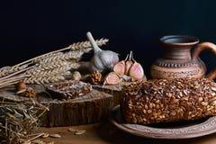 与向日葵种子、杯子牛奶,麦子大蒜和词根,坚果,健康吃的概念的黑暗的谷物面包,在一木backg 图库摄影
