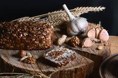 与向日葵种子、麦子大蒜和词根,坚果,健康吃的概念的黑暗的谷物面包,在st的木背景 库存图片