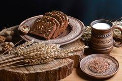 与向日葵种子的黑暗的谷物面包,杯子牛奶,亚麻籽,麦子射击,健康吃的概念,在木背景  库存照片