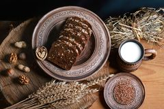 与向日葵种子的黑暗的谷物面包,杯子牛奶,坚果,亚麻籽,麦子射击,健康吃的概念,在一木backgro 库存照片