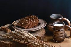 与向日葵种子的黑暗的谷物面包,杯子牛奶,麦子射击,健康吃的概念,在树桩的木背景, p 免版税库存图片