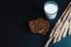 与向日葵种子的黑暗的谷物面包,杯牛奶,麦子在一个黑暗的背景页岩板,健康吃, p的概念剥落 库存图片