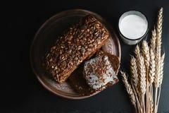 与向日葵种子的黑暗的谷物面包,杯牛奶,麦子在一个黑暗的背景页岩板,健康吃, t的概念剥落 库存图片