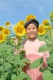 与向日葵花的逗人喜爱的亚洲女孩微笑 库存图片