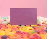 与含糖的果冻和空白的笔记薄的桃红色纸背景 r 库存照片