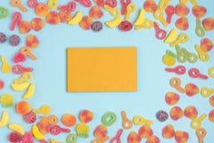 与含糖的果冻和空白的笔记薄的蓝纸背景 r 图库摄影
