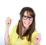 与听到在mp的音乐的earbuds/耳机的妇女跳舞 免版税库存图片