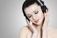 与耳机的美丽的深色的weoman 库存照片