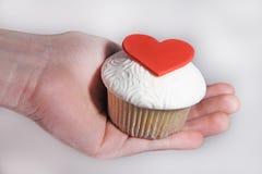 与听见的乳香树脂杯形蛋糕在女性手上 免版税图库摄影